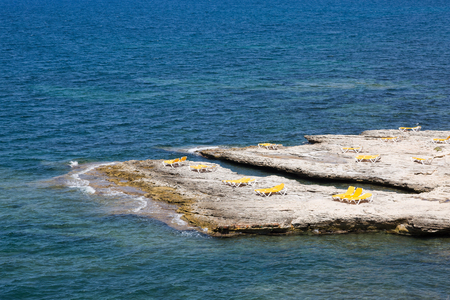 Dry rock with empty yellow deck chairs at the coast of Corsica, France Imagens - 84773800