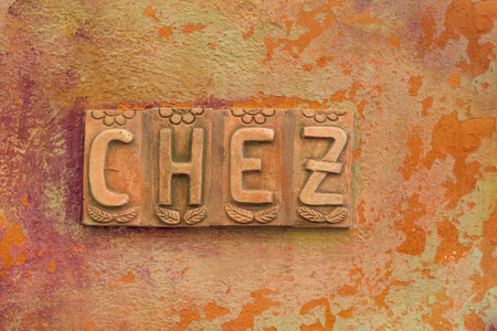 Ornate letters chez on an orange painted wall at a restaurant in Corse, France