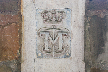 Initials of Mexican Emperor Maximilian and symbols crown and anchor on a stone wall at castle Miramare, Trieste, Italy Imagens