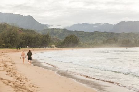 Young couple walking along Hanalei Bay beach on the island Kauai, Hawai Фото со стока