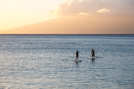 Silhouette of two standup paddlers at the north shore of Maui, Hawaii