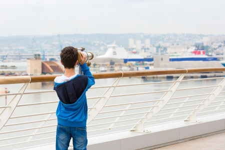 A young boy exploring the port of Marseille, France, with a telescope