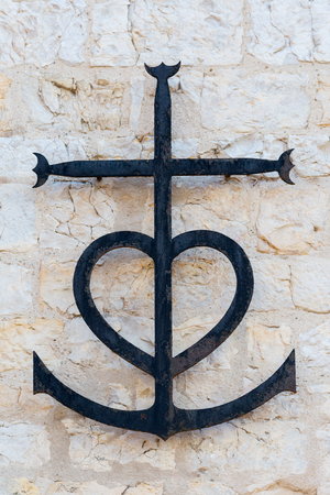 Metal Camargue cross from provencal Saintes Maries de la Mer symbolizing the three cardinal virtues: faith (cross), charity (heart) and hope (anchor)
