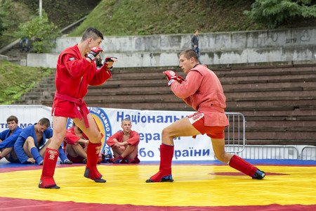 ukranian: Two adult male sambo fighters dressed in red kimono having a workout on tatami.The photo was taken during an open outdoor social event organized by Ukranian Federation of Sambo in Kiev on Independence Day, 24.08.2016.No accreditation was required. The eve