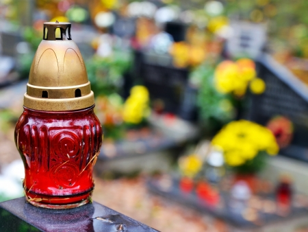 Red candle and tombs with flowers at cemetery photo