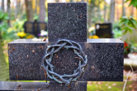 memorial candle: Granite cross with crown of thorns at cemetery