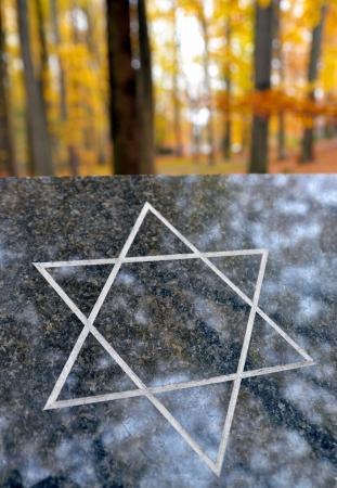 etoile juive: Dalle de granit avec une �toile juive � l'automne for�t au cimeti�re Banque d'images
