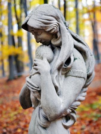 dode bladeren: Standbeeld van Madonna en kind in de herfst bos op begraafplaats Stockfoto