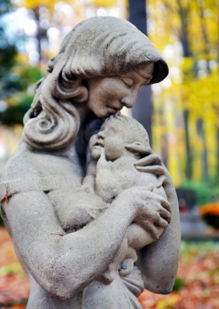 Statue of Madonna and child in autumn forest at cemetery Stock Photo - 16268509