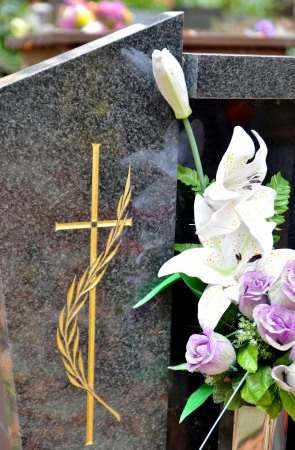 Tombstone with golden cross and flowers at cemetery Stock Photo - 16268516