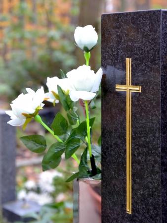 Tombstone mit goldenen Kreuz und weißen Rosen auf dem Friedhof Standard-Bild