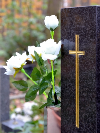 burial: Tombstone with golden cross and white roses at cemetery