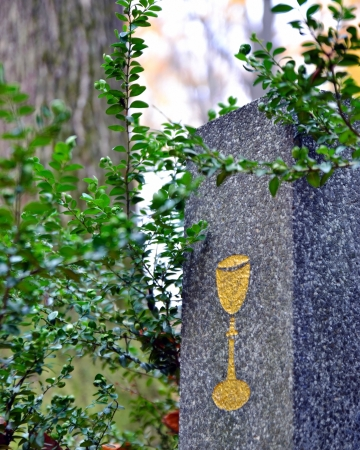 Tombstone with golden chalice and green shrub at cemetery Stock Photo - 16268517