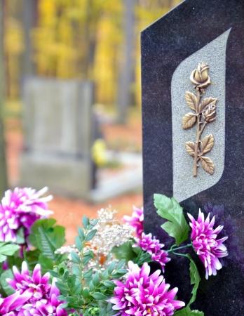 Tombstone mit goldenen Rosen und lila Blumen auf dem Friedhof Standard-Bild