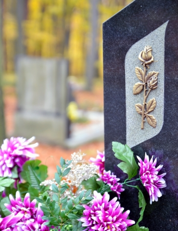 burial: Tombstone with golden rose and purple flowers at cemetery