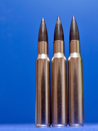 ammunition: Detail of three bullets on blue background