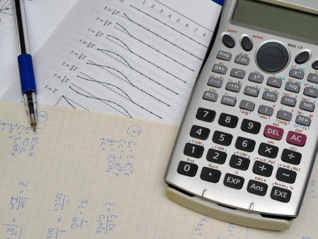 Physics calculations and notes, textbook and calculator photo