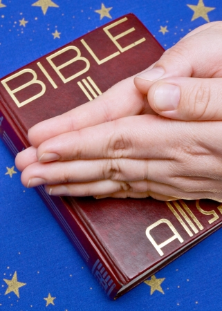 A view with a bible and praying hands photo