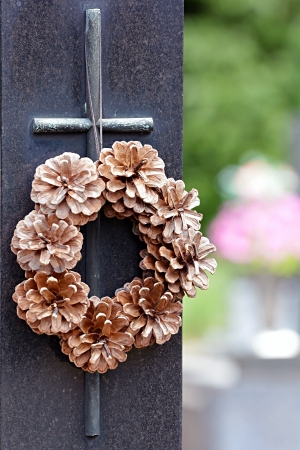 memorial cross: Cruce con una guirnalda de conos en un cementerio