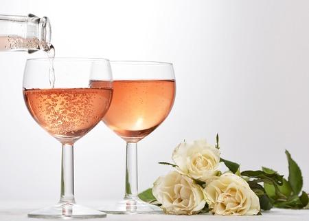 wijn glas met rode sprankelende drankje gegoten in nad witte rozen Stockfoto
