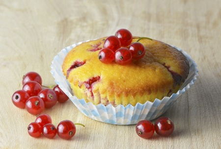 Vanilla muffin with red currant berries on wooden background photo