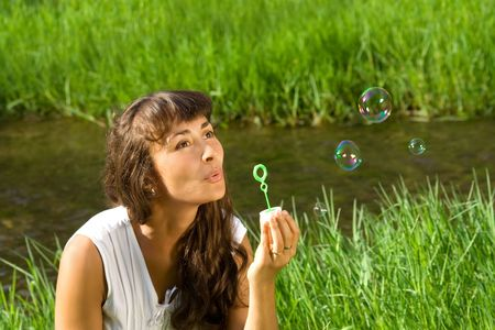 Young nice girl blowing bubbles on the meadow near the water photo