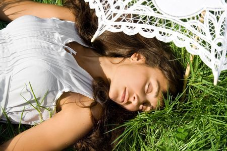 Young woman in white dress sleeping on the fresh green grass