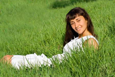 Smiling happy young girl on the meadow with green fresh grass Stock Photo