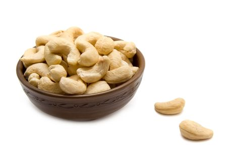 Cashew  nuts in the ceramic brown bowl isolated on white Stock Photo