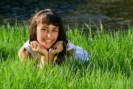 liying: Young  smiling girl liying on the fresh green grass near the river  Stock Photo