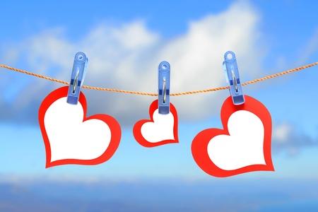 Tres corazones de secado en la cuerda en el fondo de cielo