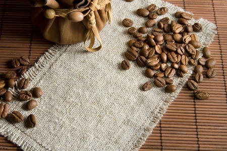 Background with roasted coffee beans and small leather pack