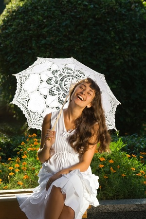 Happy attractive girl in white dress with sun umbrella sitting and laughing on the bench in the park