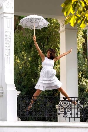 Happy young woman  jumping  with white sun umbrella