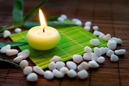 Flaming candle, white stones and bamboo leaves - a composition symbolizing meditation and inner harmony photo