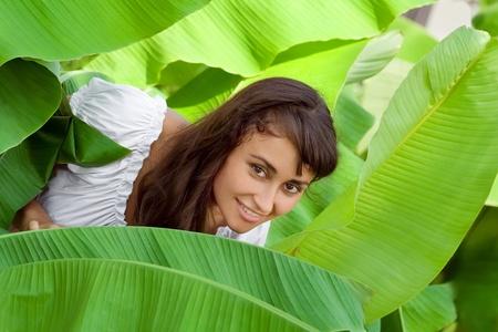 Smiling young girl having fun in banana leaves Stock Photo