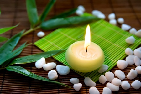 Composition with flaming candle, white  stones and bamboo leaves, symbolizing zen, calmness and meditation photo