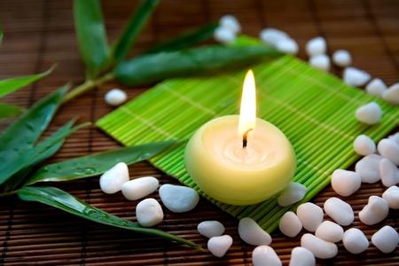 Komposition mit brennenden Kerze, weißen Steinen und Bambus Blätter, symbolisiert Zen, Stille und meditation Standard-Bild