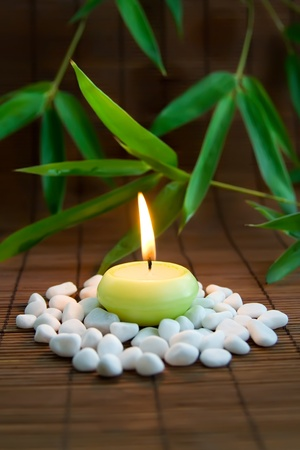 Flaming candle, white stones and bamboo leaves. Symbolizing meditation and inner harmony Stock Photo