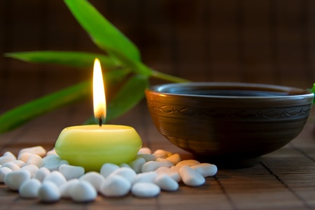 Composition with white zen stones, burning candle, bamboo leaves and clay bowl with tea symbolizing harmony, calmness and relaxation photo