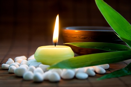 white candle: Composition with white zen stones, burning candle, bamboo leaves and clay bowl with tea symbolizing harmony, calmness and relaxation