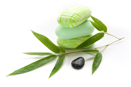 Three pieces of soap, green bamboo branches and zen stone  photo