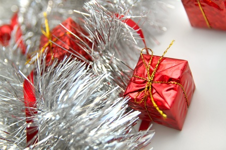 gewgaw: Christmas background with silver tinsel and red shiny gifts