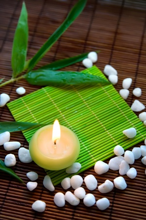 Background with stones, candle and bamboo leaves photo