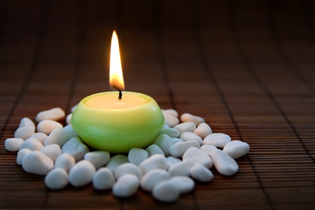 Composition with white zen stones and burning candle, symbolizing harmony, calmness and relaxation. On dark background Stock Photo