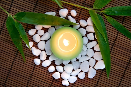 Flaming candle, white stones and bamboo leaves -  composition for meditation and inner harmony