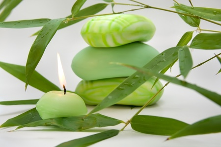 Pieces of aromatic soap, burning candle and bamboo leaves - for bath and relaxation