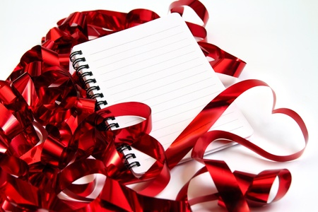 Valentine background with writing-pad and shiny red ribbons in the shape of heart photo