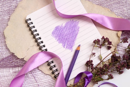 Valentine background with writing-pad, old texturized paper, herbs and shiny ribbons. Horizontal composition  photo
