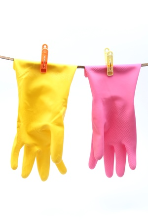 Colorful protective gloves for household chores drying on a rope - isolated